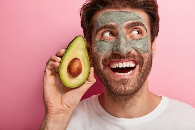 Primo piano del volto di un bell'uomo brunet con un ampio sorriso a trentadue denti, tiene una fetta di avocado vicino al viso, indossa una maschera di argilla fatta in casa nutriente per ridurre i punti oscuri, indossa una maglietta bianca casual. concetto di benessere