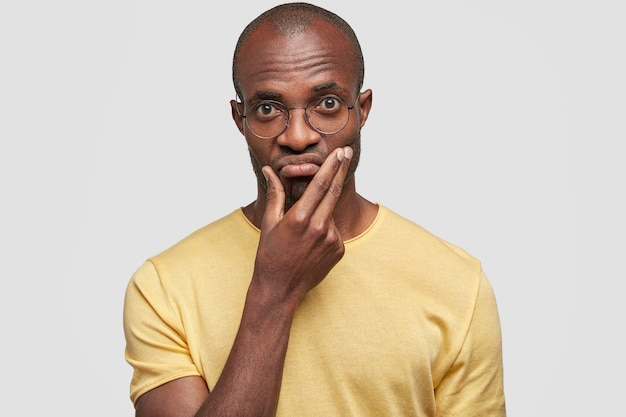 Headshot of handsome puzzled businessman with dark skin