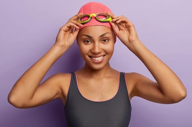 Il colpo alla testa della donna afroamericana felice tiene la mano sugli occhiali di protezione, sorride ampiamente alla macchina fotografica