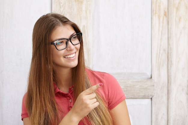 Headshot of happy beautiful girl in rectangular spectacles dressed casually pointing her index finger away looking with joyful and pleased smile, showing her white teeth. body language.