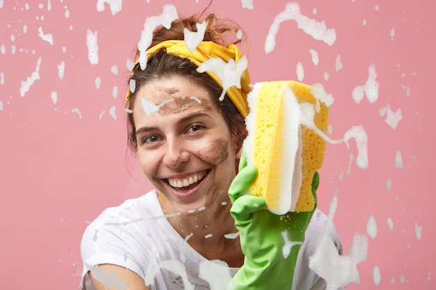 Headshot of happy beautiful positive young housewife with charming smile washing window in the kitchen, wiping out thick foam off glass surface, enjoying cleaning process, smiling