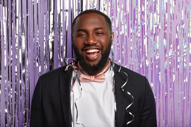 Il primo piano del volto di un uomo felice dalla pelle scura sorride ampiamente, mostra denti bianchi e splendenti, vestito con abiti formali, arriva alla festa