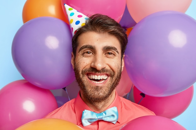 Headshot of happy european man wears paper cone hat, pink shirt and bowtie, looks positively