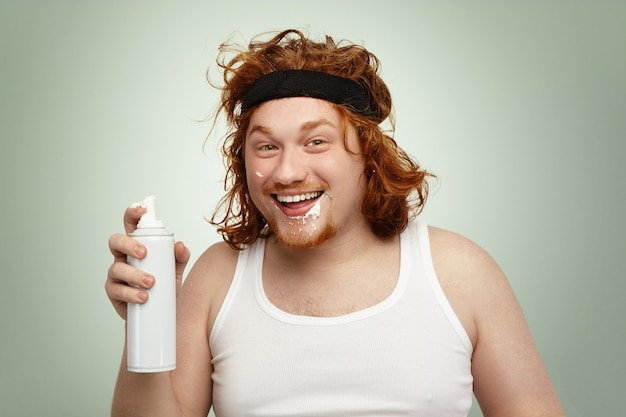 Headshot of happy excited obese young european male with curly ginger hair consuming extra calories