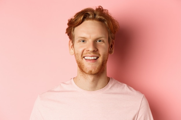 Headshot of happy redhead man with beard and white teeth, smiling excited at camera, standing over pink background.