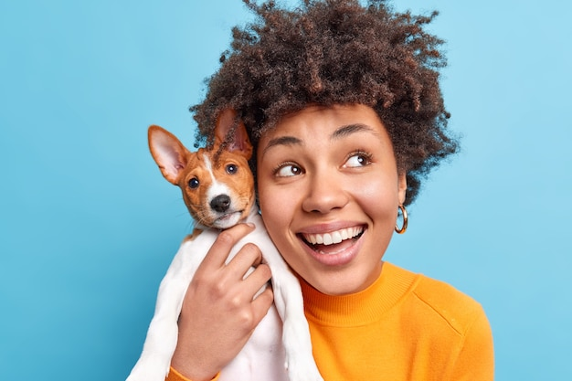 Headshot of happy smiling dark skinned afro american woman holds nice breed dog expresses positive emotions has dreamy expression going to have walk with favorite pet. people and animals concept