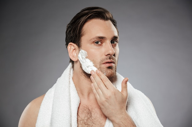 Headshot of healthy man putting shaving foam on face, while having morning skincare isolated over gray wall