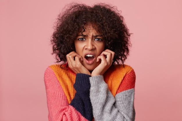 Primo piano del volto di isterica ragazza afroamericana con acconciatura afro che guarda nella disperazione e nel panico, nervoso, spaventato, tiene i pugni vicino al viso, isolato