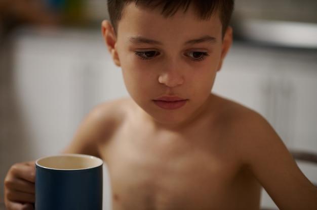뜨거운 음료와 함께 세라믹 컵을 가진 사랑스러운 소년의 얼굴만 이미지