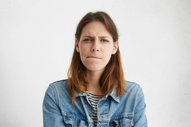 Headshot of indecisive confused young european woman in denim wear pursuing lips, her look expressing doubt and uncertainty
