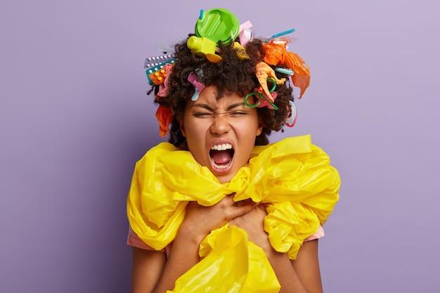 Headshot di donna infastidita irritata in posa con immondizia tra i capelli