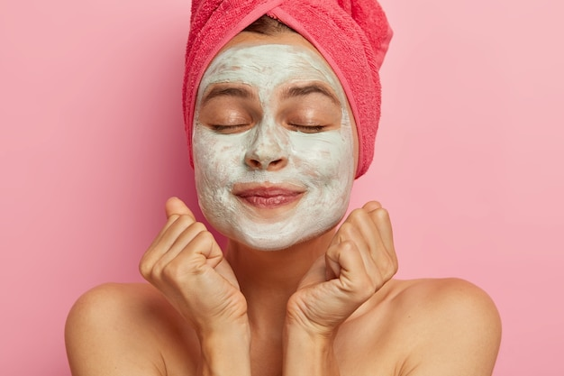 Headshot of lovely girl keeps clenched fists near face, wears facial cleansing mask, keeps eyes shut, has bare shoulders, healthy perfect skin, cares about her body