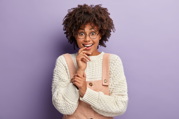 Headshot of lovely joyful young afro american woman attends party, wears stylish clothes, looks with interest, isolated over purple wall, impressed by cute desirable present.