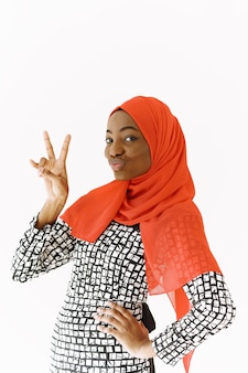 Headshot of lovely satisfied religious muslim woman with gentle smile, dark healthy skin, wears scarf on head. isolated over white background.