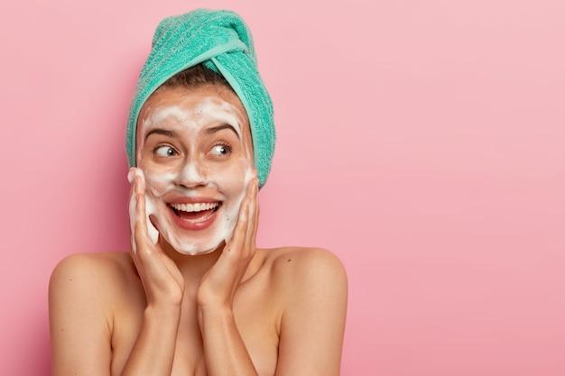 Primo piano del volto di un adorabile modello femminile sorridente che tocca le guance, guarda da parte, lava il viso con una bolla di sapone, ha il corpo nudo, indossa un asciugamano morbido turchese sulla testa, posa su un muro roseo, copia spazio per la promozione