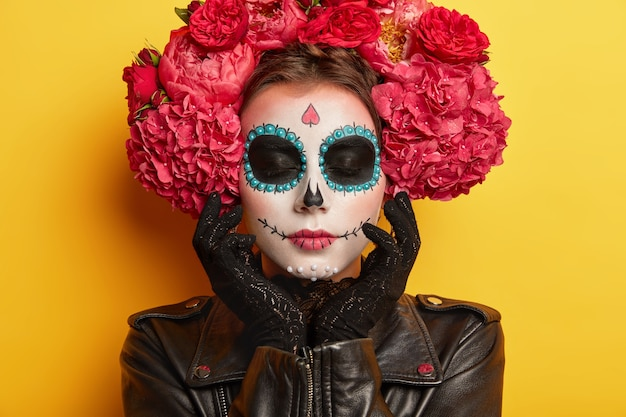 Headshot of lovely woman has painted skull, horror makeup, touches decorated face, wears black leather jacket and lace gloves, keeps eyes closed, dressed as skeleton, isolated over yellow background