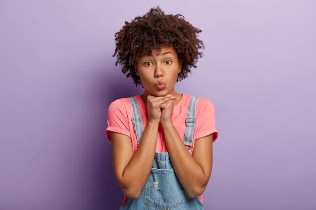 Il primo piano del volto di una donna adorabile tiene le mani sotto il mento, ha le labbra piegate, una pelle sana e scura, un'acconciatura afro