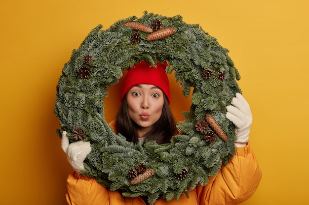 Headshot of lovely young asian woman looks through green handmade wreath, keeps lips rounded, dressed in outerwear, enjoys winter time, models against yellow studio wall.