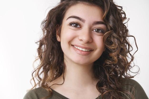 Headshot fortunato sognante carino donna armena ricci acconciatura sorridente si spera ottimista umore positivo godendo bella conversazione amichevole ghignando gioiosa in piedi sfondo bianco rilassato