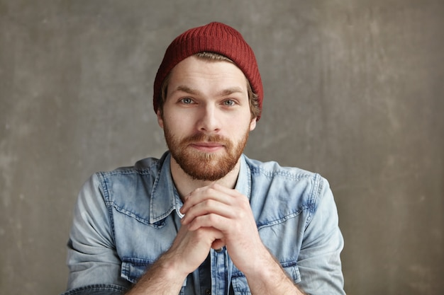 Headshot of modern good-looking young european hipster wearing stylish hat and blue jeans shirt holding hands clasped in front of him, having thoughtful and dreamy look, sitting at concrete wall
