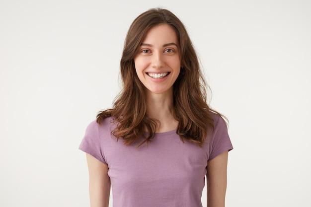 Headshot di bella giovane donna attraente, piacevolmente sorridente guardando direttamente la fotocamera, indossa una maglietta viola