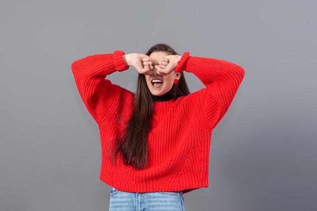 赤いセーターとジーンズに身を包んだ長い髪の幸せな感情的な10代の少女のヘッドショット