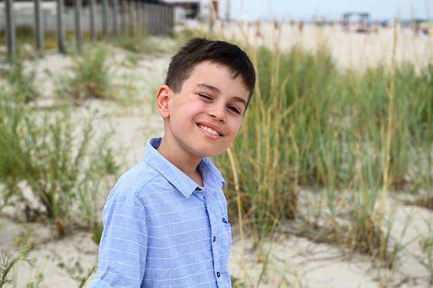 Выстрел в голову очаровательного ребенка, мило улыбающегося, стоящего на фоне степных зарослей и песчаной почвы. красивый ребенок мило улыбается, глядя в камеру.