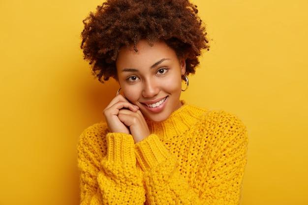 사랑스러운 로맨틱 한 여성의 얼굴 만은 즐거운 미소를 가지고 있고, 손에 머리를 기울이고, 부드러운 표정을 가지고 있으며, 검은 곱슬 머리를 가지고 있으며, 아늑한 겨울 스웨터를 입고 노란색 배경 위에 절연되어 있습니다.