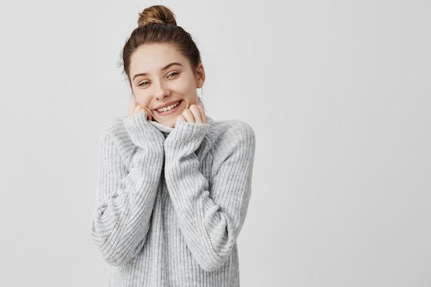 灰色のセーターの襟で顔を包み込む愛らしい笑顔の女性のヘッドショット。緩和と快適さを表現する女性アーティスト。気持ちのコンセプト
