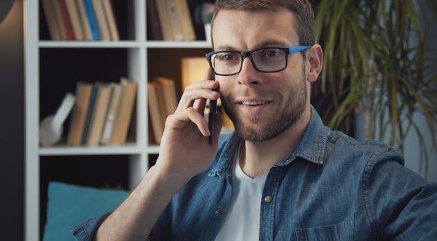 Выстрел в голову взрослого бородатого мужчины в очках и джинсовой рубашке, говорящего по смартфону в квартире