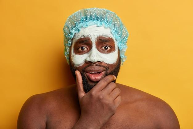 Афро-мужчина держится за подбородок, наносит маску из глиняной грязи для здоровой кожи, выглядит обеспокоенным, носит шапочку для душа.