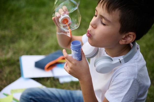 Выстрел в голову школьника начальной школы, отдыхающего в парке, сидящего на зеленой траве после школы и пускающего мыльные пузыри. школьная сумка с учебниками и школьными принадлежностями, лежа на траве