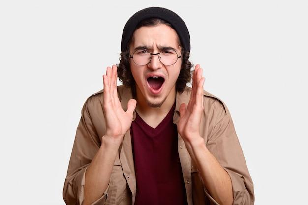 화가 절망적 인 힙 스터 남자의 얼굴 만 넓게 입을 열고, 입 근처에 두 손을 유지하고, 자극으로 외치며, 둥근 안경과 검은 모자를 쓰고 흰색 스튜디오 벽 위에 절연