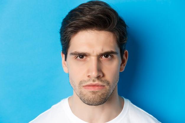 青い背景の上に立って、眉をひそめ、失望し、悩んでいるように見える怒っている男のヘッドショット