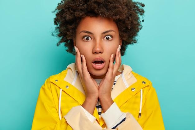 놀란 아프리카 여성의 얼굴 사진은 충격적인 소식을 믿지 못하고 손바닥으로 뺨을 만지며 놀라움으로 입을 벌리고 노란 비옷을 입고 두려움과 당혹감을 표현합니다.