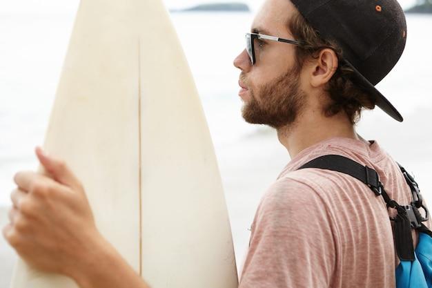 세련된 수염을 가진 매력적인 백인 남자의 얼굴 만, 패들 보드를 들고 사려 깊은 표정을하고 서핑 훈련을 준비하는 동안 바다 파도를보고