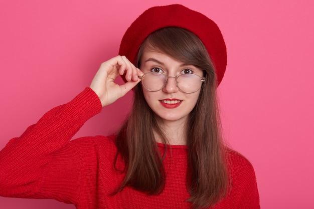 魅力的なdarkhaired女性のヘッドショットはメガネのフレームに手を保ち、彼女の目、セーターとベレー帽を身に着けている女性を信じられない