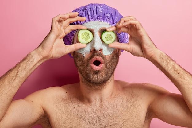 매력적인 남성의 얼굴 사진은 페이셜 트리트먼트 절차가 있고, 눈에 오이 조각을 유지하고, 클레이 마스크를 쓰고, 샤워 캡을 쓰고, 셔츠없이 혼자 서 있습니다.