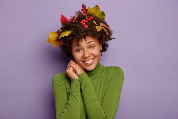 魅力的な若い巻き毛の女性のヘッドショットは、恥ずかしがり屋のフレンドリーな陽気な表情をしており、顔の近くに手を保ち、カジュアルに立って、緑のタートルネックを着て、紫色の背景に対してポーズをとっています。