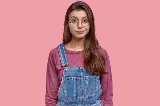 Выстрел в голову красивой молодой девушки-брюнетки, которая думает о проблеме, демонстрирует смущенные эмоции, носит джинсовый комбинезон, поджимает губы