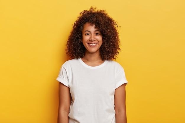 美しいダークスキンのカーリーのヘッドショットは、表情を喜ばせ、成功を喜ばせ、暇な時間を楽しんで、黄色の壁に隔離されたカジュアルなtシャツを着ています。人々、前向きな感情、感情の概念