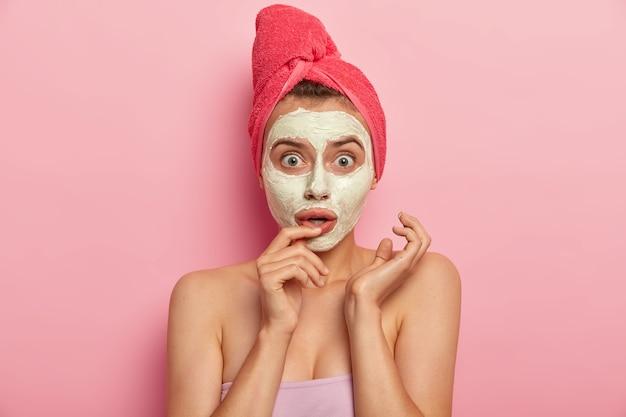 아름다운 유럽 여성의 얼굴 사진은 천연 점토 마스크를 적용하고, 스파 살롱을 방문하고, 분홍색 부드러운 수건을 착용하고, 반응이 멍청하고, 몸에 관심이 있고, 실내 모델을 돌 봅니다. 각질 제거, 신선함, 피부 관리