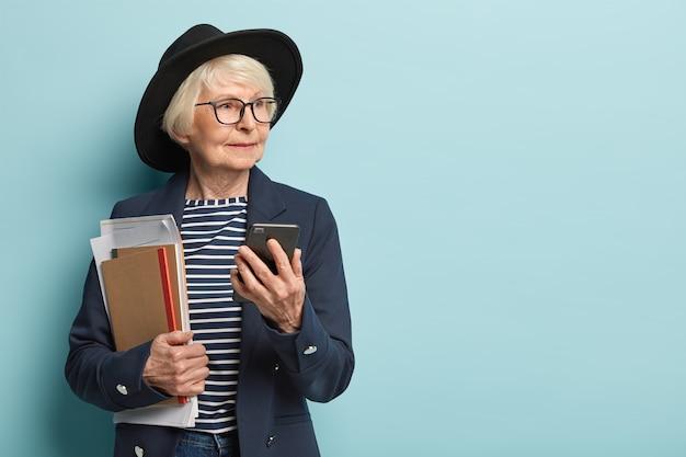 아름다운 노부인의 얼굴은 옆으로 보이고 사려 깊은 표정을 지으며 온라인 채팅에서 문자 메시지를 보냅니다.
