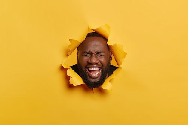 형태가 이루어지지 않은 흑인의 얼굴 만은 기쁨에서 웃고, 즐거워하고, 찢어진 노란색 배경에 포즈를 취하고, 이빨 미소를 짓고, 하얀 치아를가집니다.