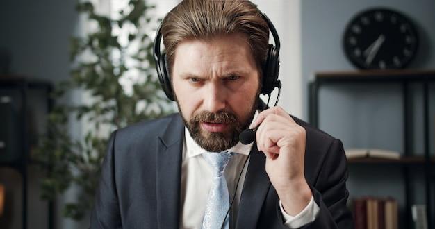 Выстрел в голову бизнесмена, касающегося микрофона гарнитуры, имеющего удаленный разговор через интернет