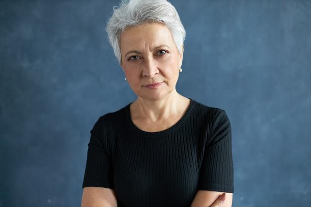 カジュアルな服装の60歳の引退した女性のヘッドショット。白髪で腕を胸に組んで、不審な表情でカメラを見つめ、目を細めている。