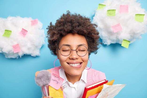 홈 오피스 연구에서 주간 계획 스티커로 둘러싸인 쾌활한 아프리카 계 미국인 여성의 얼굴만은 에세이가 노트북 폴더와 펜을 보유하고 있습니다.