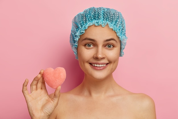 행복한 표정, 부드러운 미소, 완벽한 이빨을 가진 쾌활한 유럽 여성의 얼굴 만은 샤워 캡을 쓰고 작은 심장 모양의 스폰지를 들고 샤워를하고 깨끗하고 건강한 피부를 가지고 있습니다. 위생 개념