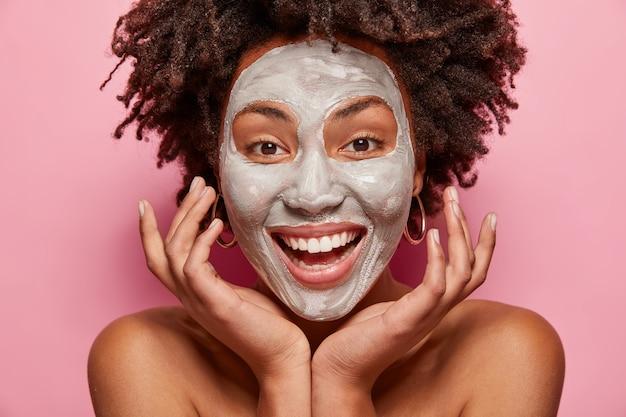 흰 점토 마스크를 가진 쾌활한 소녀의 얼굴 사진은 얼굴을 만지고 피부와 아름다움을 돌보고 긍정적 인 미소, 아프로 헤어 스타일, 분홍색 벽 위에 모델, 실내 포즈를 취합니다. 페이셜 트리트먼트 컨셉