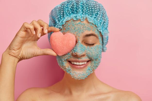 크리스탈 바다 소금 스크럽을 가진 쾌활한 젊은 여성의 얼굴 사진, 눈에 분홍색 하트 모양의 스폰지를 들고 긍정적으로 미소 짓고 샤워 캡을 착용하고 분홍색 벽에 모델을 쓰고 모공에서 얼굴을 벗 깁니다.